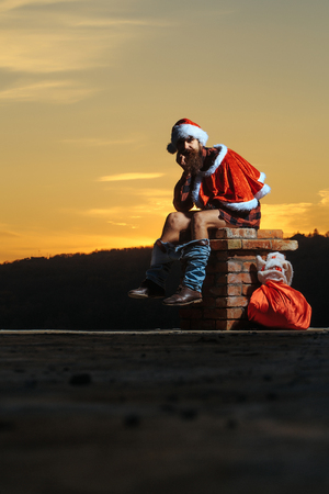 young handsome bearded bad santa claus man with long beard in checkered shirt jeans and red new year hat in christmas or xmas coat with toy sack shits or poops on brick chimney in sunset