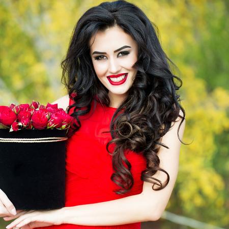 sexy young girl: молодая красивая сексуальная женщина или девушка с милой улыбкой лицо и длинные волосы брюнетки имеет модный макияж с красной помадой и платье держит букет цветов розы в коробке на естественный фон