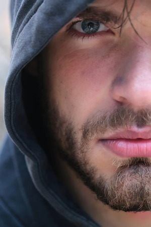 Bearded man young handsome guy male with beard and half face grey eye in hood on head outdoors