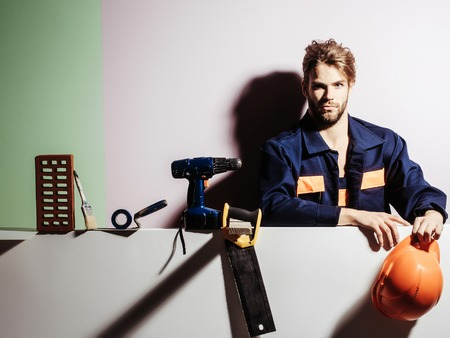 Handsome man bearded blond male builder repairman craftsman foreman or construction worker in orange hard hat and boilersuit with technical tools on colorful background