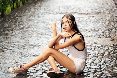 Mooie meid schattige mooie vrouw met nat haar en kleren zit op geplaveide weg in waterdruppels buitenshuis onder zomerregen Stockfoto