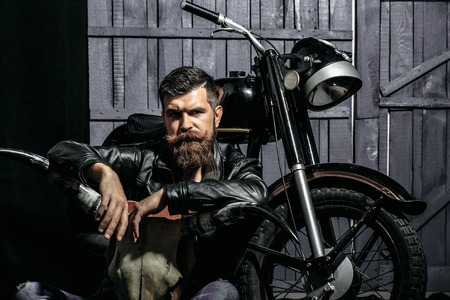 Bearded man hipster biker brutal male with beard and moustache in leather jacket sits on floor near motorcycle with bone skull antlers on wooden background Archivio Fotografico