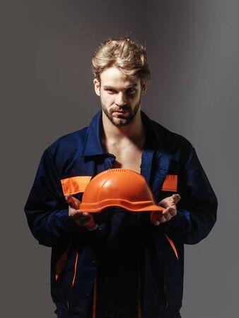 boilersuit: Handsome man builder construction mason worker repairman craftsman foreman blond bearded male in boilersuit keeps orange hard hat in hands on grey background Stock Photo