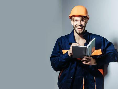 boilersuit: Happy man smiling handsome builder repairman craftsman foreman or construction worker in orange hard hat and boilersuit keeps accounting book on grey background Stock Photo