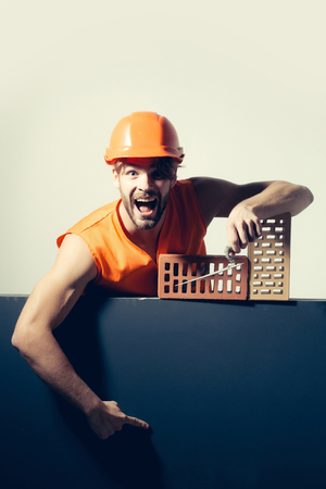 macho: young handsome bearded macho man screaming builder with sexy muscular athletic strong body has strong hands in orange uniform and hard hat or helmet with brick and tool
