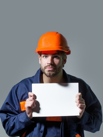 boilersuit: Surprised man handsome builder construction mason worker repairman craftsman foreman bearded male in boilersuit and orange hard hat keeps blank paper for copy space in hands on grey background Stock Photo