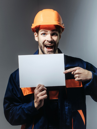 boilersuit: Excited man handsome builder construction mason worker repairman craftsman foreman bearded male in boilersuit and orange hard hat keeps blank paper for copy space in hands on grey background Stock Photo