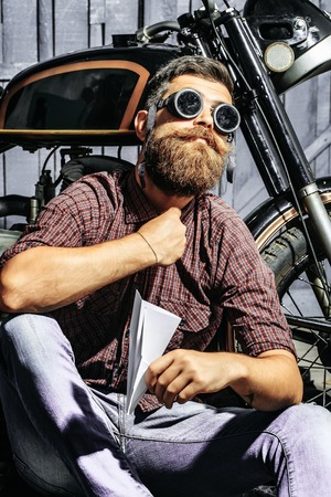 Bearded man hipster biker brutal male with beard and moustache in shirt sits on floor near motorcycle with paper plane in sunglasses on wooden background