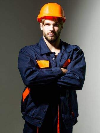 boilersuit: Handsome man builder construction mason worker repairman craftsman foreman in orange hard hat and boilersuit stands with arms crossed on grey background
