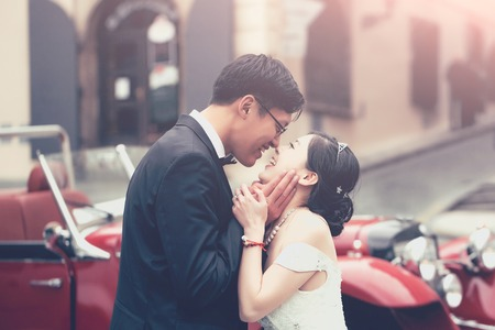 Chinese cute bride and groom young newlyweds just married couple kiss on streets of old city on wedding day in long white wedding dress stands outdoors near red retro car Фото со стока