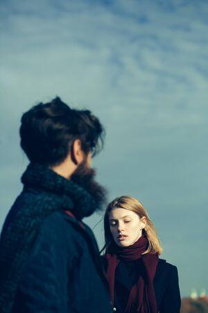 conversaciones: Bastante joven mujer hermosa con el pelo y la bufanda roja habla con inconformista hombre de la barba al aire libre en el parque en el día de otoño en el cielo azul