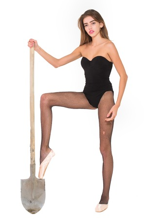 Pretty girl young cute beautiful woman or ballerina in ballet shoes and sexy black bodysuit and fishnet stockings pantyhose lingerie with shovel isolated on white Stock Photo