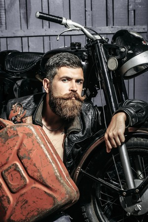 gas can: Bearded man hipster biker brutal male with beard and moustache in leather jacket sits near motorcycle with rusty metallic gas can on wooden background