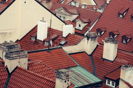 dormer: Terracotta tiled roofs with chimneys and dormer windows of city or town houses buildings on roofscape background