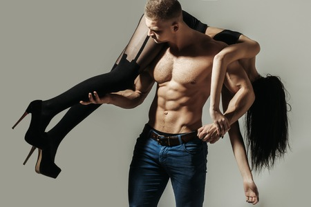 young couple of handsome macho man in jeans with sexy muscular athletic body has strong belly with six pack or abs on bare torso holds girl in black shoes and stockings with long brunette hair on grey