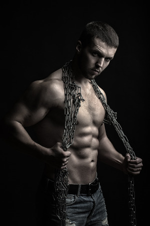 One handsome sexual strong young man with muscular body in blue jeans holding rope with hands hanging on neck and shoulders standing posing in studio on black background, vertical picture Stock Photo