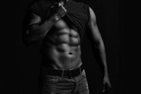 sexual anatomy: One handsome sexual strong young man with muscular body in jeans with shirt on shoulder standing posing on studio background black and white, horizontal picture
