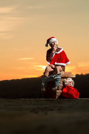 young bearded bad santa claus man with long beard in checkered shirt jeans and red new year hat in christmas or xmas coat with toy sack shits or poops on brick chimney in sunset smoking cigarette