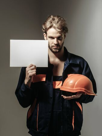 boilersuit: Serious man handsome builder construction mason worker repairman craftsman foreman blond bearded male in boilersuit keeps orange hard hat and paper for copy space in hands on grey background
