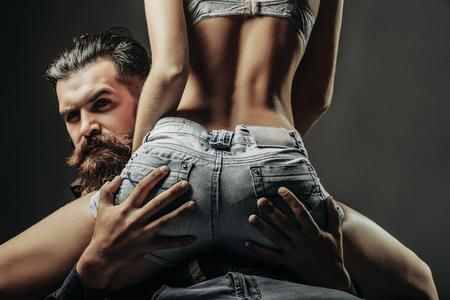 髭のハンサムな男と若いきれいな女性または灰色の背景にジーンズのショート パンツでセクシーなお尻を持つ少女の女性のスリムな柔軟なボディ