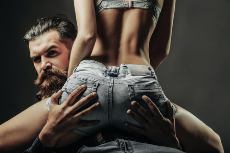 bearded handsome man and female slim flexible body of young pretty woman or girl with sexy buttocks in jeans shorts on grey background Stok Fotoğraf - 67563225