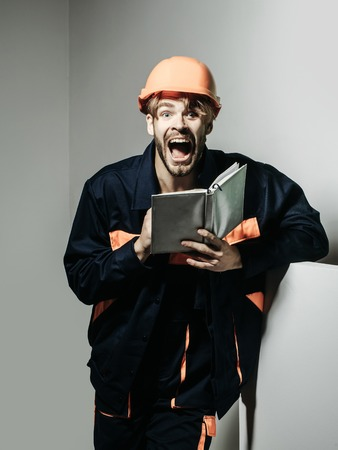 boilersuit: Excited man shouting handsome builder repairman craftsman foreman or construction worker in orange hard hat and boilersuit keeps accounting book on grey background Stock Photo