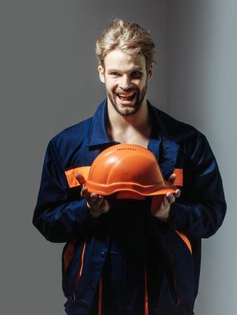 boilersuit: Excited man handsome builder construction mason worker repairman craftsman foreman blond bearded male in boilersuit keeps orange hard hat in hands on grey background