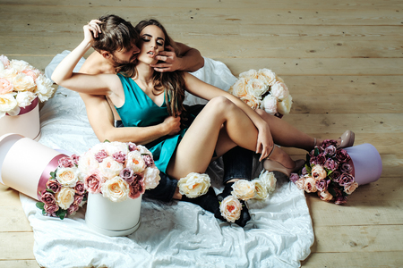 Sexy couple young beautiful cute lovers in love pretty girl and sexi man with boxes of flowers hug on wooden floor
