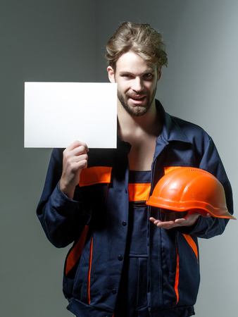 boilersuit: Smiling man handsome builder construction mason worker repairman craftsman foreman blond bearded male in boilersuit keeps orange hard hat and paper for copy space in hands on grey background