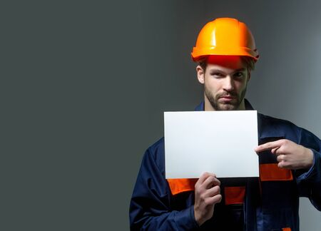 boilersuit: Serious man handsome builder construction mason worker repairman craftsman foreman bearded male in boilersuit and orange hard hat keeps blank paper for copy space in hands on grey background Stock Photo