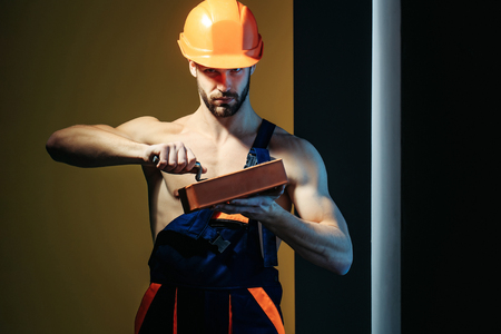 macho: young handsome bearded macho man builder with sexy muscular athletic strong body has strong hands in blue uniform and orange hard hat or helmet holds brick and spatula
