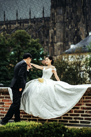 中国かわいい新郎新婦若い新婚の夫婦はちょうど結婚幸せなカップルの結婚式の日に古い都市の路上キス