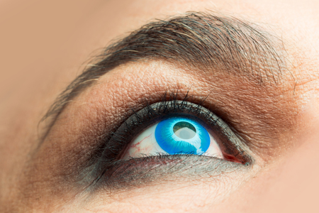 wrinkled brow: Senior man with blue color lens in eye and bushy eyebrows with eyelashes on old wrinkled face Stock Photo