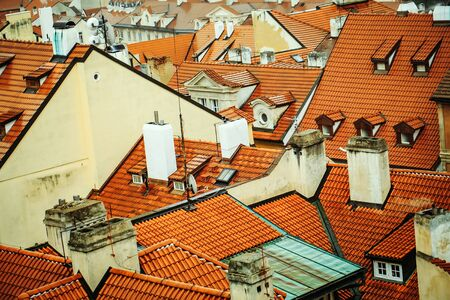 Terracotta tiled roofs with chimneys and dormer windows of city or town houses buildings on roofscape background