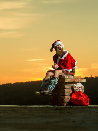 young handsome emotional bearded bad santa claus man with long beard in checkered shirt jeans and red new year hat in christmas or xmas coat with toy sack shits or poops on brick chimney in sunset Reklamní fotografie