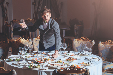 dirty blond: Handsome young man with beard and blond hair eats vegetables with wine in glass from dirty plates with leftovers or residues of food after banquet dinner on table in restaurant Stock Photo