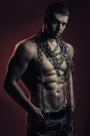 sexual anatomy: One handsome sexual strong young man with muscular body in blue jeans holding rope with hands in pockets hanging on neck and shoulders standing posing in studio on red background, vertical picture Stock Photo