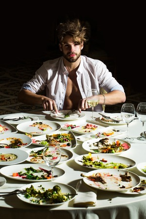unbutton: Handsome man or sexy muscular macho athlete in unbutton shirt eats with fork and knife at table with leftovers or residues food on dirty plates after banquet in restaurant on dark background