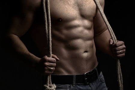 sexual anatomy: One handsome sexual strong young man with muscular body in blue jeans holding rope with hands hanging on neck and shoulders standing posing in studio on black background, horizontal picture Stock Photo