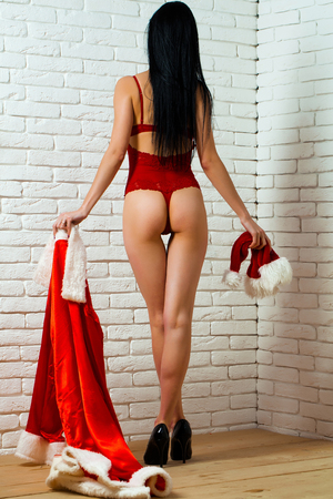Pretty girl with sexy back buttocks cute ass and sexi slim legs in red lingerie with traditional santa claus Christmas new year suit hat and coat on white brick background Stock Photo