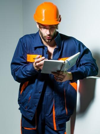 boilersuit: Handsome man builder repairman craftsman foreman or construction worker in orange hard hat and boilersuit keeps accounting book on grey background