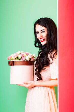 young pretty sexy woman or girl with cute smiling face and long brunette hair has fashionable makeup with red lipstick in dress holds pink rose flowers bouquet in box on green background