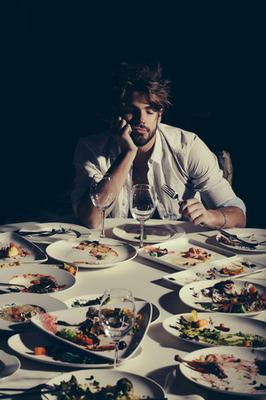 dirty blond: Handsome man with beard and blond messy hair bored or tired sleeping at table with leftovers or residues food on dirty plates after banquet dinner in restaurant on dark background