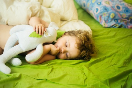 sleeps: Cute baby boy child with blond curly hair sleeps peacefully with soft toy in bed on green sheet