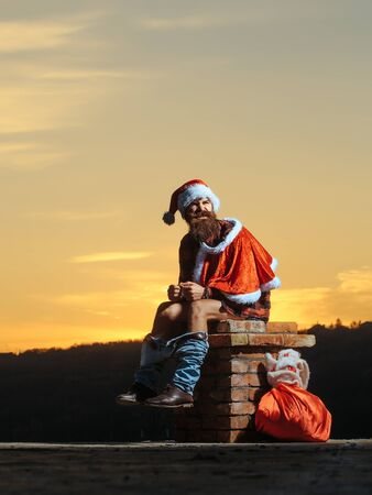young handsome emotional bearded bad santa claus man with long beard in checkered shirt jeans and red new year hat in christmas or xmas coat with toy sack shits or poops on brick chimney in sunset Stock Photo