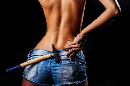 Sexy female buttocks sexi back in blue denim shorts jeans with iron metallic hammer and nail in pocket on dark background Stock Photo