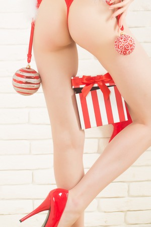 sexy female legs of santa claus in fashionable shoe with present or gift new year box for christmas or xmas red color on white brick wall background and wood or wooden floor Stock Photo