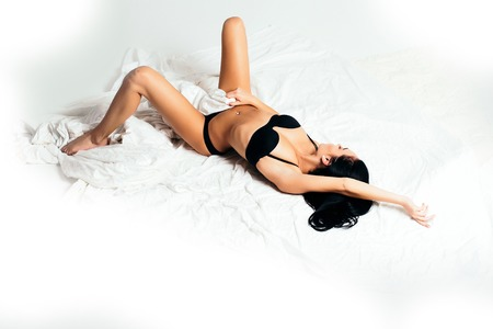 young pretty woman or fashionable sexy girl with cute face and brunette hair in black lingerie lying on white linen in morning bed with bare belly on beautiful body