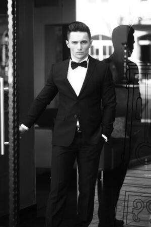 opens: Man young handsome in elegant suit with bow tie opens glass entrance door to street black and white on urban background