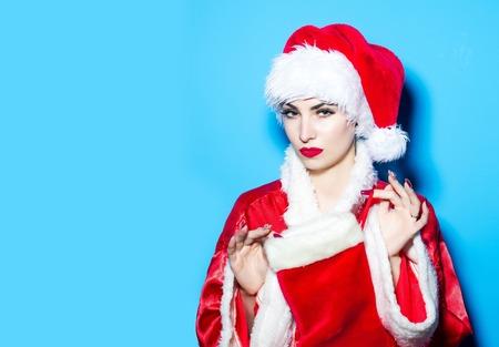 poses de modelos: Bastante hermosa joven modelo de mujer atractiva mujer linda en el sombrero rojo tradicional de Papá nuevo año y traje plantea con el calcetín de Navidad sobre fondo azul Foto de archivo